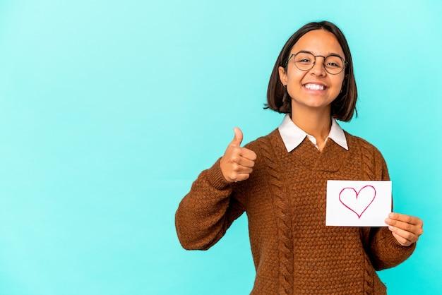 Giovane donna ispanica di razza mista in possesso di un cuore di carta sorridente e alzando il pollice