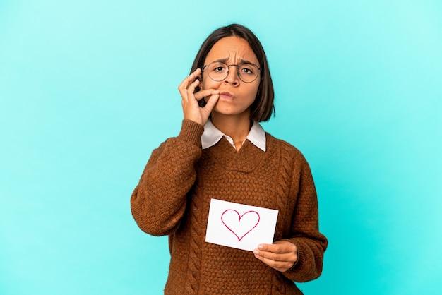 Giovane donna ispanica di razza mista che tiene una carta di cuore con le dita sulle labbra mantenendo un segreto.