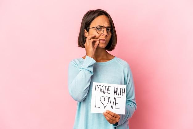 Giovane donna ispanica di razza mista che tiene un poster di carta fatto con amore con le dita sulle labbra mantenendo un segreto.