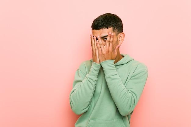 Il giovane uomo di sport ispanico sbatte le palpebre attraverso le dita spaventato e nervoso.