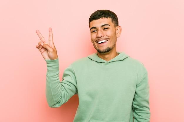 Giovane uomo di sport ispanico gioioso e spensierato che mostra un simbolo di pace con le dita.