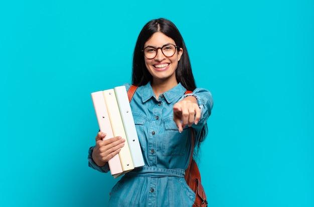 Donna giovane studentessa ispanica che punta alla telecamera con un sorriso soddisfatto, fiducioso, amichevole, scegliendo te