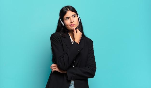 Giovane donna ispanica telemarketer pensando, sentendosi dubbiosa e confusa, con diverse opzioni, chiedendosi quale decisione prendere