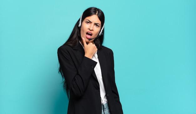 Giovane donna ispanica telemarketer con la bocca e gli occhi spalancati e la mano sul mento, sentendosi spiacevolmente scioccata, dicendo cosa o wow