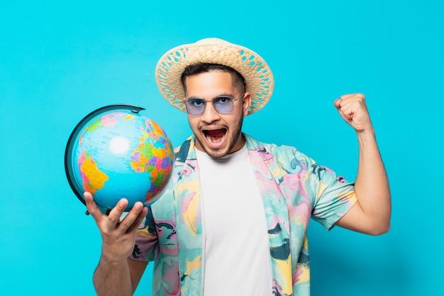 Uomo giovane viaggiatore ispanico che celebra con successo una vittoria e tiene un globo del mondo