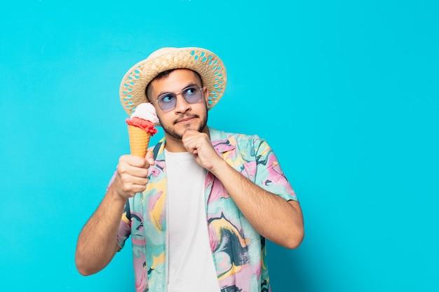 Giovane viaggiatore ispanico che dubita o dell'espressione incerta e tiene in mano un gelato