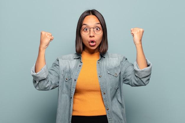 Giovane donna ispanica che celebra un incredibile successo come un vincitore