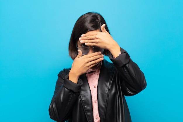 Fronte della copertura della giovane donna ispanica con entrambe le mani che dicono no alla macchina fotografica! rifiutare le foto o vietare le foto