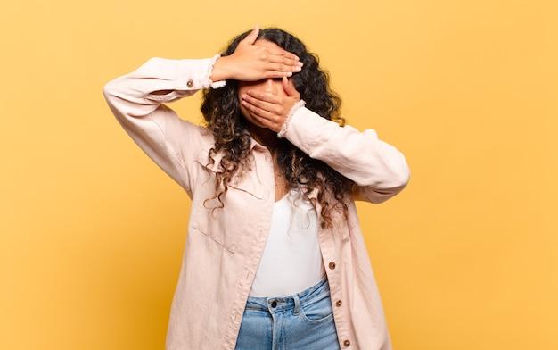 Giovane donna ispanica che copre il viso con entrambe le mani dicendo no alla telecamera! rifiutare le foto o vietare le foto