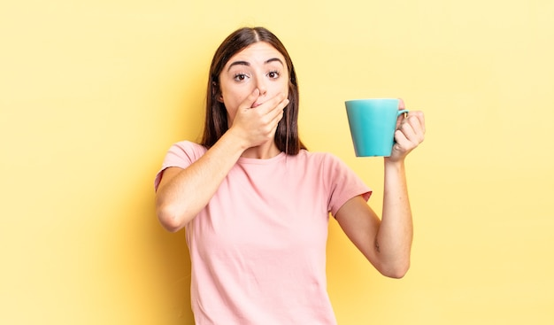 Giovane donna ispanica che copre la bocca con le mani con uno scioccato. concetto di tazza di caffè
