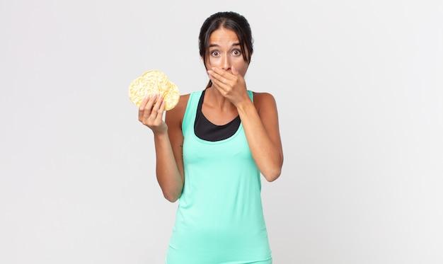 Giovane donna ispanica che copre la bocca con le mani con uno scioccato. concetto di dieta fitness