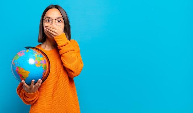 Giovane donna ispanica che copre la bocca con le mani con un'espressione scioccata e sorpresa, mantenendo un segreto o dicendo oops