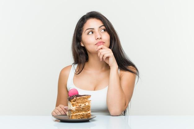 Giovane donna ispanica che mangia una torta che guarda lateralmente con espressione dubbiosa e scettica.