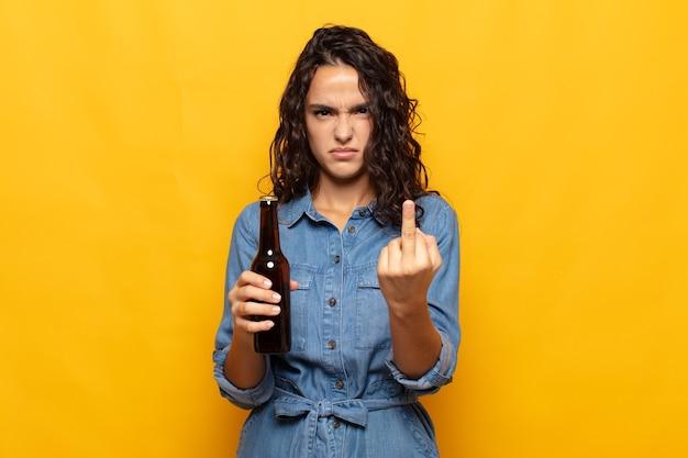 Giovane donna ispanica che si sente arrabbiata, infastidita, ribelle e aggressiva, lancia il dito medio, reagisce