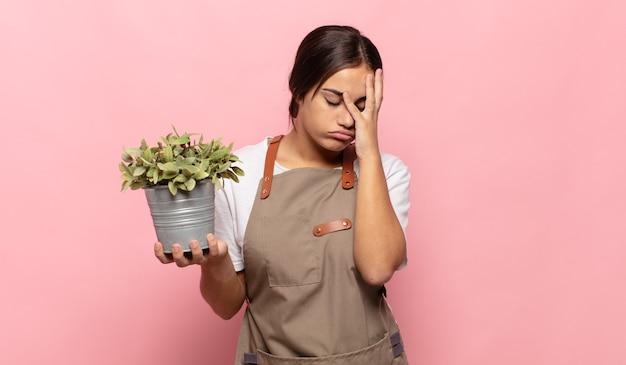 Giovane donna ispanica che si sente annoiata, frustrata e assonnata dopo un compito noioso, noioso e noioso, tenendo la faccia con la mano