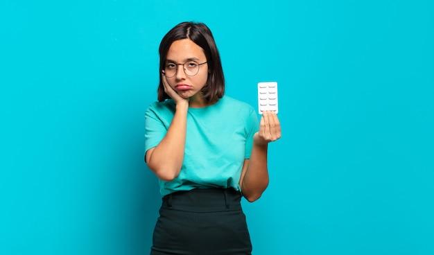Giovane donna ispanica che si sente annoiata, frustrata e assonnata dopo un compito noioso, noioso e noioso, tenendo il viso con la mano