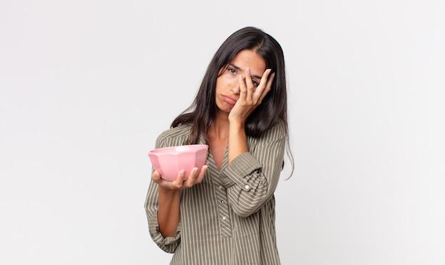 Giovane donna ispanica che si sente annoiata, frustrata e assonnata dopo una noiosa e con in mano una ciotola o una pentola vuota