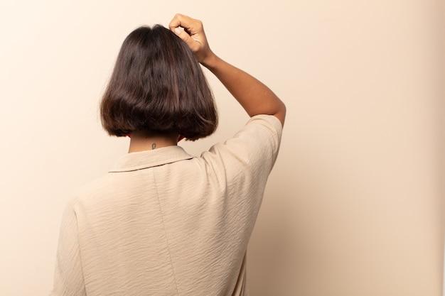 Giovane donna ispanica che si sente incapace e confusa, pensando a una soluzione, con la mano sull'anca e l'altra sulla testa, vista posteriore