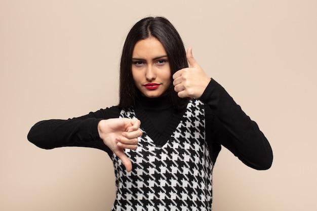 Giovane donna ispanica che si sente confusa, incapace e insicura, valutando il bene e il male in diverse opzioni o scelte