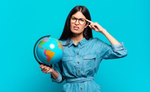 Giovane donna ispanica che si sente confusa e perplessa, dimostrando che sei pazzo, pazzo o fuori di testa. concetto di pianeta terra