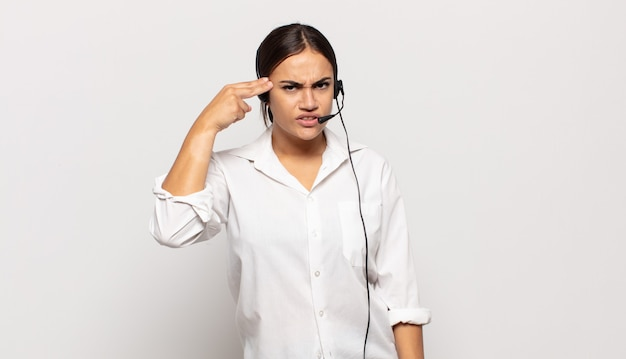 Giovane donna ispanica che si sente confusa e perplessa, dimostrando che sei pazzo, pazzo o fuori di testa
