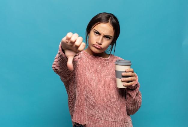 Giovane donna ispanica che si sente arrabbiata, arrabbiata, infastidita, delusa o scontenta, mostrando i pollici verso il basso con uno sguardo serio