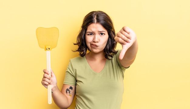 Giovane donna ispanica che si sente croce, mostra i pollici in giù. uccidere mosche concetto