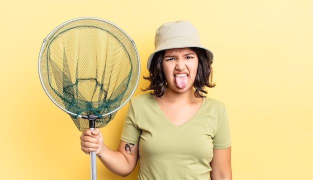 Giovane donna ispanica che si sente disgustata e irritata e con la lingua fuori. concetto di rete da pescatore