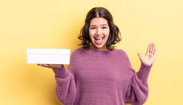 Giovane donna ispanica che si sente felice e stupita per qualcosa di incredibile. concetto di scatola vuota