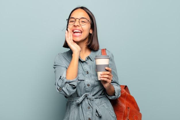 Giovane donna ispanica che si sente felice, eccitata e positiva, dando un grande grido con le mani vicino alla bocca