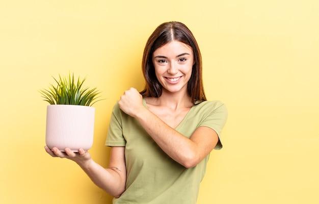 Giovane donna ispanica sentirsi felice e affrontare una sfida o festeggiare. concetto di vaso per piante