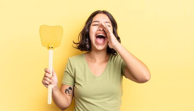 Giovane donna ispanica sentirsi felice, dando un grande grido con le mani vicino alla bocca. uccidere mosche concetto
