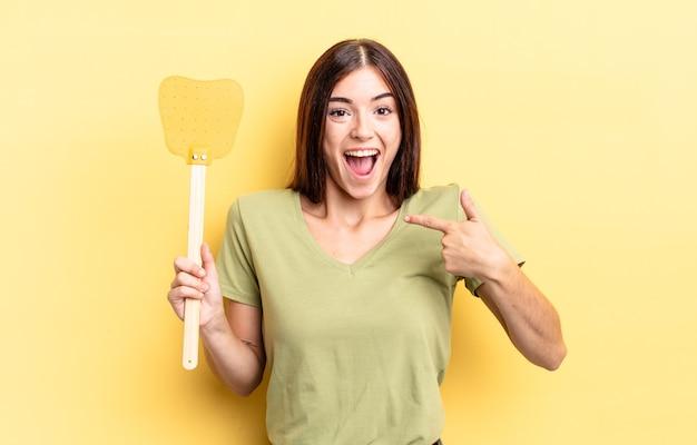 Giovane donna ispanica sentirsi felice e indicarsi con un eccitato. uccidere mosche concetto