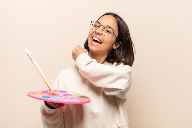 Giovane donna ispanica che si sente felice, positiva e di successo, motivata quando affronta una sfida o celebra buoni risultati