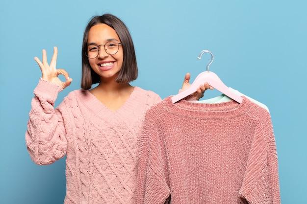Giovane donna ispanica che si sente felice, rilassata e soddisfatta, mostrando l'approvazione con il gesto giusto, sorridendo