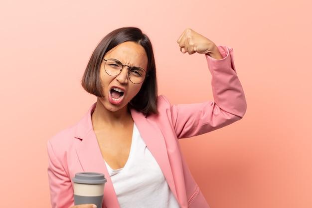 Giovane donna ispanica che si sente felice, soddisfatta e potente, che flette in forma e bicipiti muscolosi, sembra forte dopo la palestra