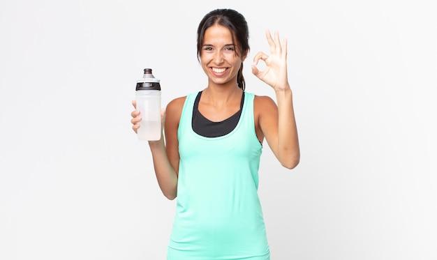 Giovane donna ispanica che si sente felice, mostra approvazione con un gesto ok e tiene in mano una bottiglia d'acqua. concetto di fitness