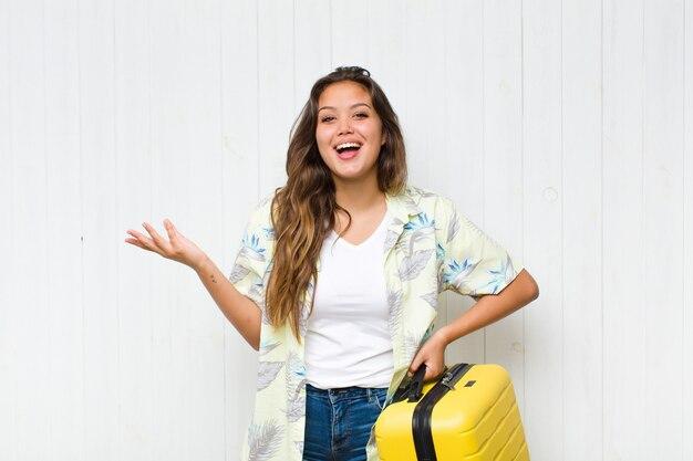 Giovane donna ispanica che si sente felice, sorpresa e allegra, sorridente con atteggiamento positivo, realizzando una soluzione o un'idea