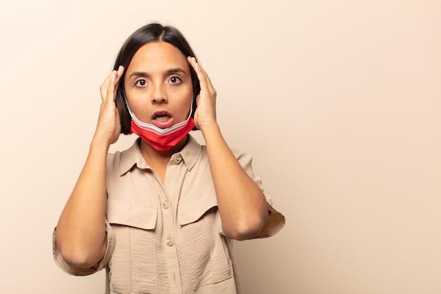 Giovane donna ispanica che si sente inorridita e scioccata, alza le mani sulla testa e si fa prendere dal panico per un errore
