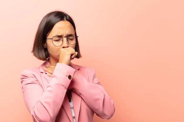 Giovane donna ispanica che si sente male con mal di gola e sintomi influenzali, tosse con la bocca coperta