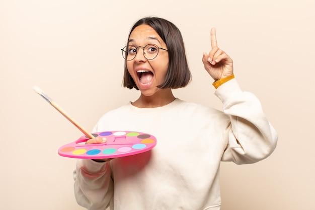 Giovane donna ispanica che si sente come un genio felice ed eccitato dopo aver realizzato un'idea, alzando allegramente il dito, eureka!