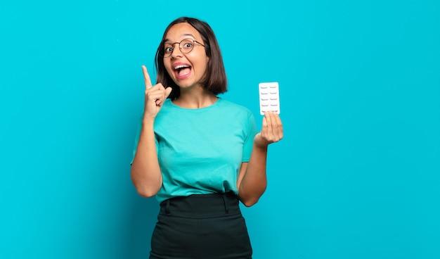 Giovane donna ispanica che si sente un genio felice ed eccitato dopo aver realizzato un'idea, alzando allegramente il dito, eureka!