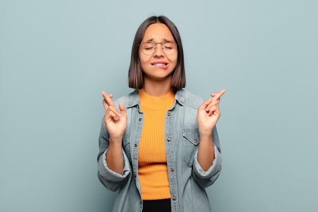 Giovane donna ispanica che si sente nervosa e piena di speranza, incrociando le dita, pregando e sperando in buona fortuna