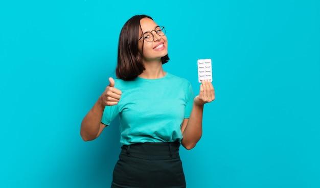 Giovane donna ispanica che si sente orgogliosa, spensierata, sicura e felice, sorridendo positivamente con i pollici in su
