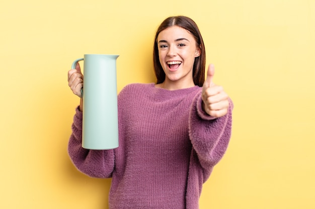 Giovane donna ispanica che si sente orgogliosa, sorride positivamente con i pollici in su. concetto di thermos per caffè