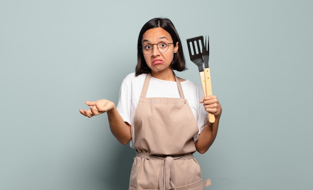 Giovane donna ispanica che si sente perplessa e confusa, dubita, appesantisce o sceglie diverse opzioni con un'espressione divertente