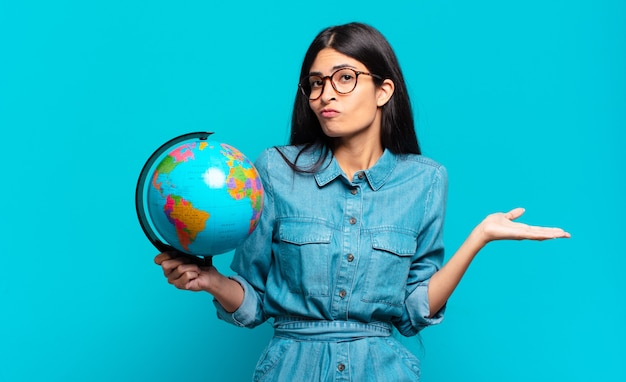 Giovane donna ispanica che si sente perplessa e confusa, dubita, appesantisce o sceglie diverse opzioni con un'espressione divertente.