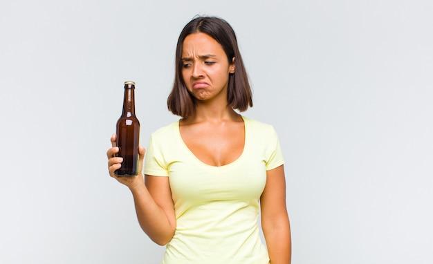 Giovane donna ispanica che si sente triste, sconvolta o arrabbiata e guarda di lato con un atteggiamento negativo, accigliata in disaccordo