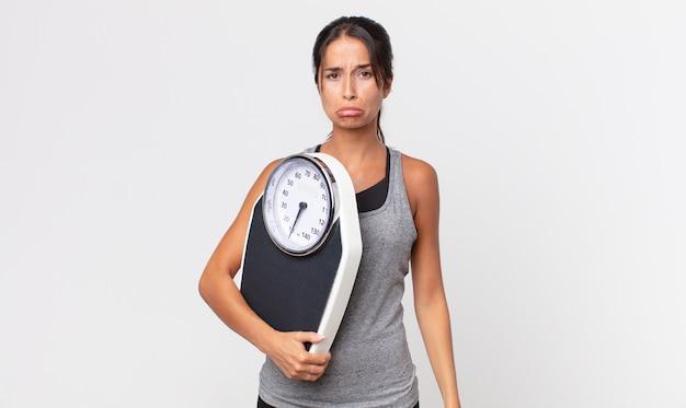 Giovane donna ispanica che si sente triste e piagnucolona con uno sguardo infelice e piange e tiene in mano una bilancia. concetto di dieta