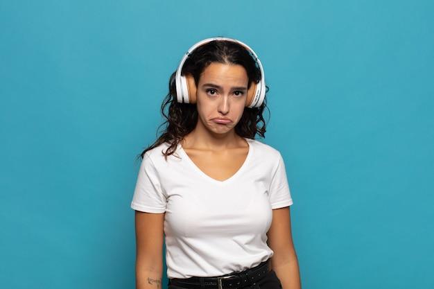 Giovane donna ispanica che si sente triste e piagnucolona con uno sguardo infelice, piange con un atteggiamento negativo e frustrato